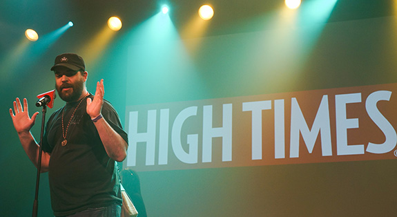 A man stands on stage during a smokey High Times Cannabis Cup with his hands held up in the air.
