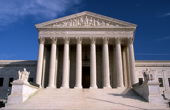 The U.S. Supreme Court building is seen from the front on a lightly clouded sunny day.