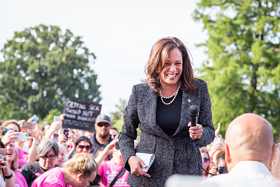 California Senator Kamala Harris smiles while standing amidst a crowd of supporters during an outdoor rally.
