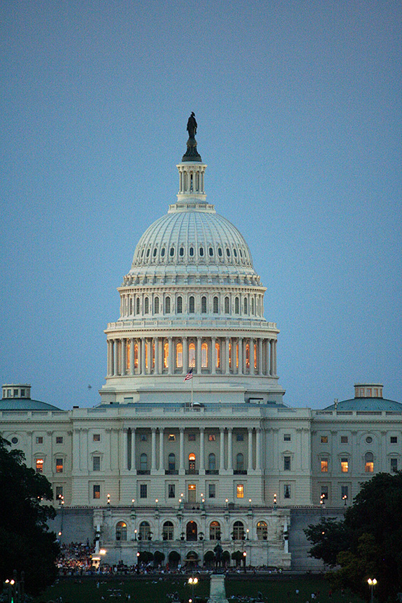 The U.S. Capitol Building in Washington, DC is seen in a closely cropped shot in early dusk as yellow lights start to glow within. It looks to be summer, with green grass and people walking around on the lawn outside.