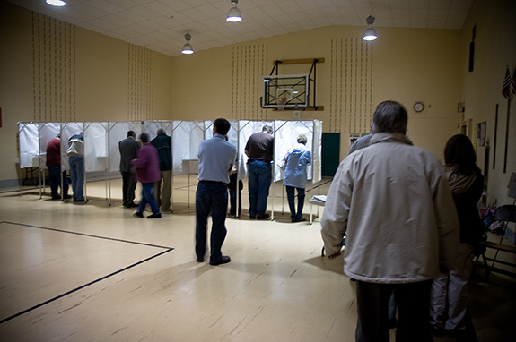 A small town community center is seen being used as a voting station with eight voting booths setup on stage side-by-side with a small line of people checking in with two women seated at a table.