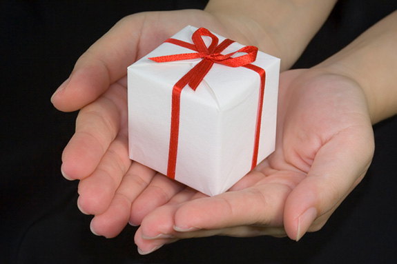 Two hands of what appears to be a white man holds a small cube-shaped gift box wrapped in plain white wrapping paper and a red ribbon with a bow on top. The hands and gift sit against a black background.