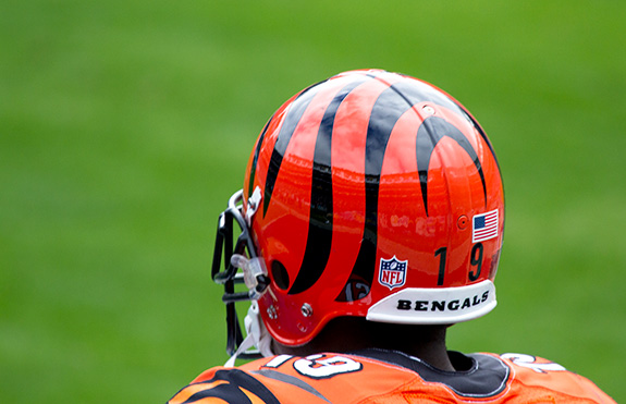 The back of a Cincinnati Bengals football player is seen close up as the player looks away from the camera with a blurry green grassy background.