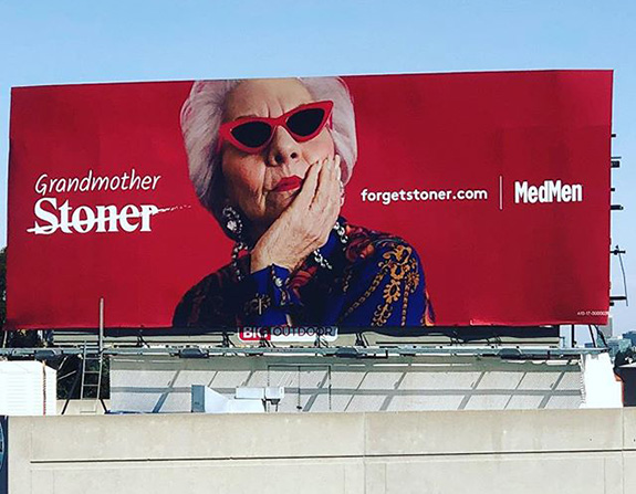 A large red MedMen billboard is seen from street level showing a grandmother wearing cool red glasses along with the word 'stoner' crossed out and replaced with the word 'grandmother'.