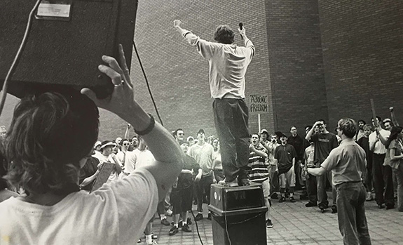 A black and white photo shows activist Shea Gunther from the back standing on a trash cash giving a speech to a rowdy crowd of college students on a campus. A sign language interpreter holds his hands up mid-sign as a fellow college student is seen to the left holding a large speaker on his head pointed toward the crowd.