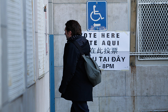 A man is seen walking into a polling station at a school, with his face mostly unseen as he turns to profile, a sign reading 'vote here' on the wall behind him taped on a grey stone wall. A handicap sign with a left-pointing arrow is affixed to the wall above the sign.