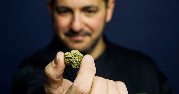 Jeff the 420 Chef holds a marijuana bud up to the camera in sharp focus while his face and black jacket are blurred in the back. He stands, smiling slightly, against a dark blue background.