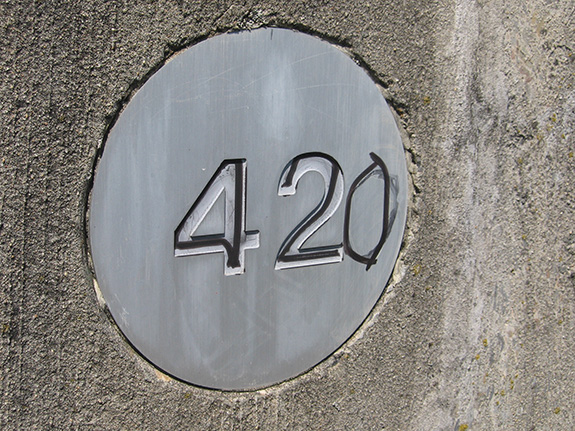 A rough concrete wall is seen close up with a metal address circle sign plate set in with an engraved
