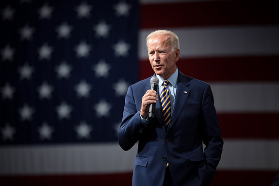 Presumptive Democratic presidential nominee Joe Biden stands alone on stage holding a microphone against a perfectly-blurred background of an American flag. Biden wears a dark blue suit and is well lit by the stage lights as he speaks.