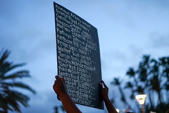 A hand-hand sign is held aloft during a protest reading the names of black people recently killed by police. 20 names are listed with each followed by the word