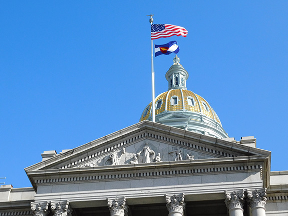 The golden Colorado state capitol building dome is seen with the American and state flags flying in front of it.