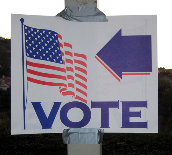 A white sign with a blue and red American flag graphic and the words VOTE is duct-taped to a metal utility pole. There is a large blue arrow on the sign above the text pointing to the right.