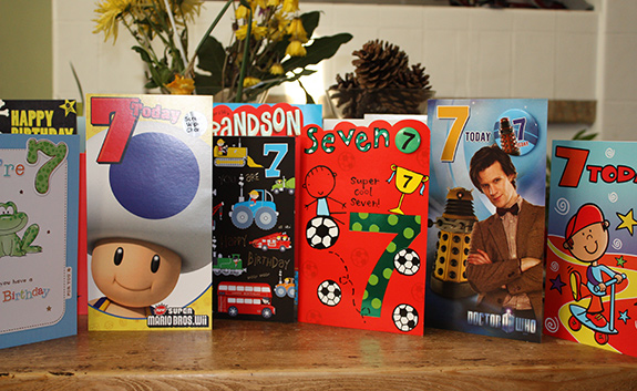 A table is seen filled with birthday cards for a 7-year-old boy, including a Super Mario Bro. card as well as one with Dr. Who on it. There are dried yellow flowers and a pinecone arrangement behind the line of cards.