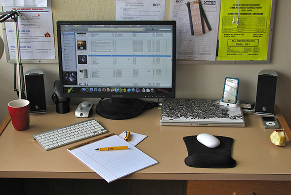 A generic looking desk in some generic looking office is seen. There is a folded up laptop on the table as well as a notepad and wireless keyboard and mouse with safety notices posted on the wall behind the flatscreen monitor.