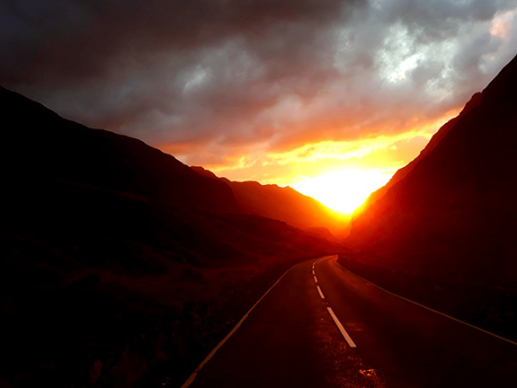 The sun appears to be setting within a mountain pass with dark thick grey clouds bordering the top of frame. The sun is bright yellow-orange in the triangle of space that it holds between the mountainous slopes. The white-dashed road is lit up and highlighted by the fading sun.
