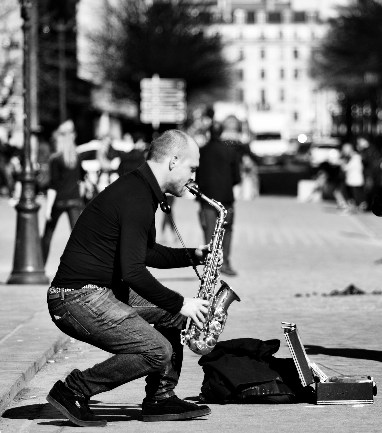 A man is seen squatting down while soulfully playing a saxophone on a city street. The photo is black and white.